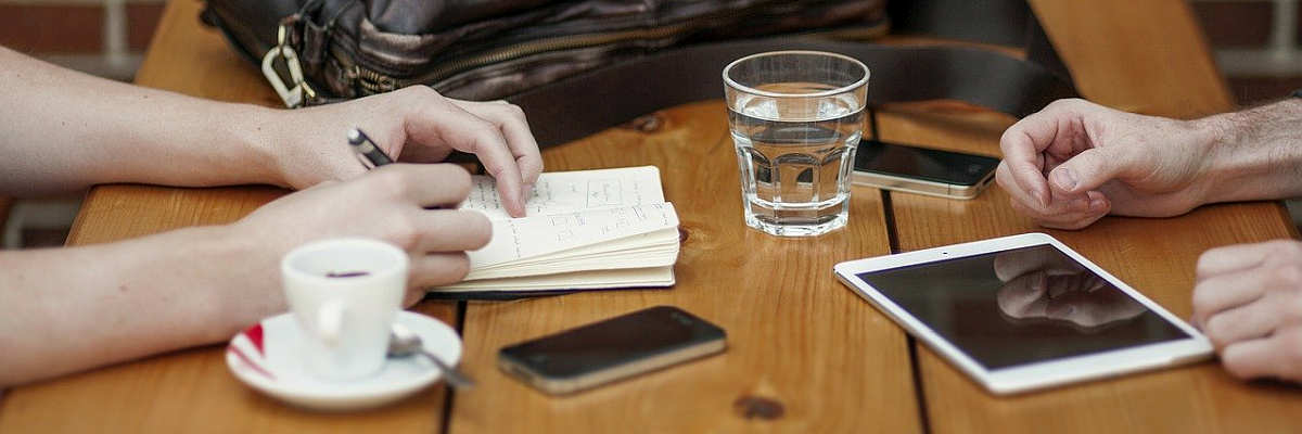 two hands on table with phone and blocnote